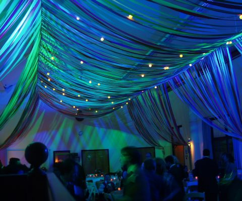 colourful-ribbon-canopy-wedding-reception-town-village-hall-celebration-beautiful-oculux-lighting-late-evening